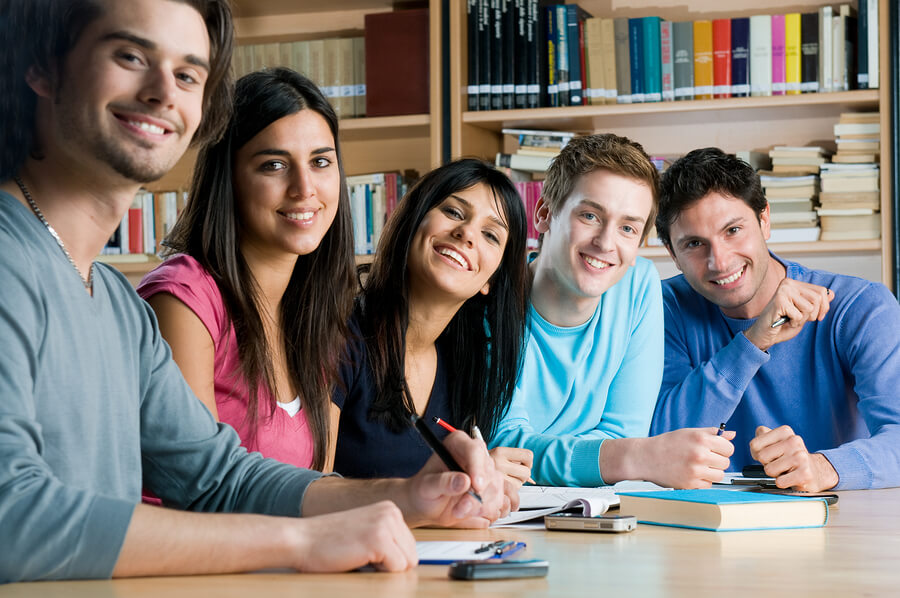 Happy group of young students studying together in a college library and looking at camera smiling